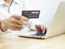Young man using credit card while shopping online. Young man entering credit card information while shopping online using laptop computer Stock Photos
