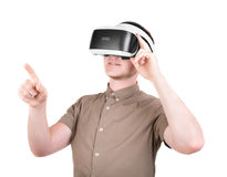 A young man is using a 3D virtual reality headset, isolated on a white background. New and professional audio equipment. royalty free stock images