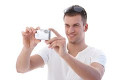 Young man using digital camera smiling Royalty Free Stock Photos