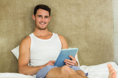 Young man using a digital tablet in bedroom Royalty Free Stock Photo