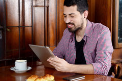 Young man using digital tablet at a cafe. Portrait of young latin man using digital tablet with cup of coffee and smartphone at a cafe. Indoor Royalty Free Stock Image