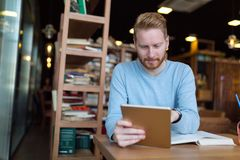 Young man using digital tablet in coffee shop royalty free stock photography