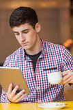 Young man using digital tablet while holding coffee cup Stock Image