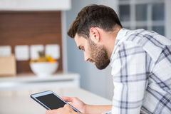 Young man using digital tablet while leaning on table Stock Photos