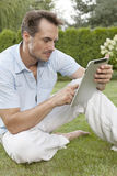Young man using digital tablet while sitting on grass in park Royalty Free Stock Photo