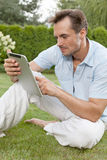 Young man using digital tablet while sitting on grass in park Royalty Free Stock Image