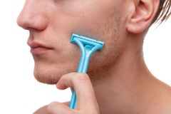 Man using a disposable razor, isolated on white background. A young man using a disposable blue razor shaves his bristle, isolated on a white background