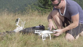 Young man using drone in the mountains stock video