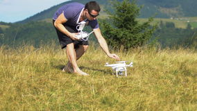 Young man using drone in the mountains stock footage