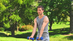 Young man using dumbells Royalty Free Stock Images