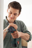 Young Man Using Electric Drill In House Renovation Project Royalty Free Stock Photography