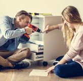 Young man using electronic drill home moving concept stock image