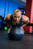 Young man using exercise ball in gym Royalty Free Stock Image