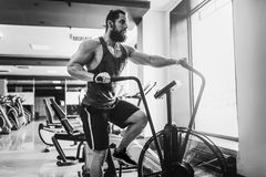 Young man using exercise bike at the gym. Fitness male using air bike for cardio workout at crossfit gym. Man using exercise bike at the gym. Fitness male using Royalty Free Stock Images