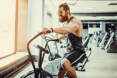Young man using exercise bike at the gym. Fitness male using air bike for cardio workout at crossfit gym. Man using exercise bike at the gym. Fitness male using Royalty Free Stock Photos
