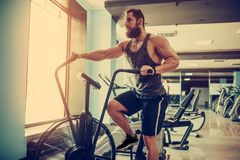Young man using exercise bike at the gym. Fitness male using air bike for cardio workout at crossfit gym. Man using exercise bike at the gym. Fitness male using Stock Photos