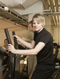 Young man using an exercise machine Stock Image