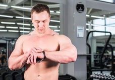 Young man using fitness bracelet during sports training in the gym.  Stock Image