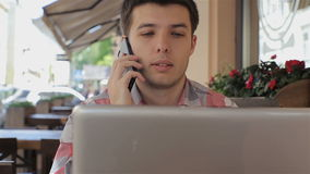 Young man using his laptop in cafe and talking on smartphone smiling happy.  stock footage
