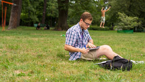 Young man using his laptop on the grass. Stock Photography