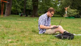 Young man using his laptop on the grass. Royalty Free Stock Image