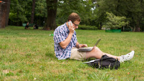 Young man using his laptop on the grass. Stock Photos