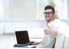 Young man using his laptop, and showing thumb up. Close up. Side view of young man using his laptop in bright living room Royalty Free Stock Photography