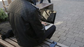 Young man using his laptop on a street bench.man typing on his laptop.  stock video footage