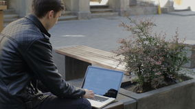 Young man using his laptop on a street bench.man typing on his laptop stock footage