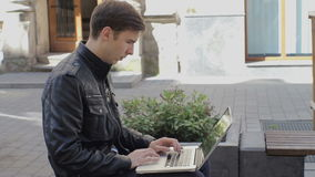 Young man using his laptop on a street bench. stock video footage