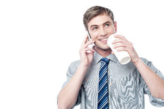 Young man using his mobile while drinking coffee royalty free stock photos