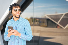 Young man using his phone and listening music close up isolated happy outdoor Royalty Free Stock Images