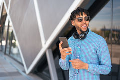 Young man using his phone and listening music close up isolated happy outdoor Royalty Free Stock Image