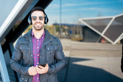 Young man using his phone and listening music close up isolated happy outdoor Stock Photo