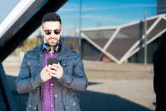 Young man using his phone and listening music close up isolated happy outdoor Royalty Free Stock Photos