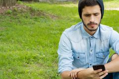 Young man using his phone. Outdoors. Portrait of young latin man using his smartphone. Outdoors royalty free stock photography