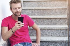 Young man using his phone stock photography