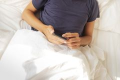 Young man using his smartphone in bed Royalty Free Stock Photo