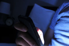 Young man using his smartphone in bed at night Royalty Free Stock Photo