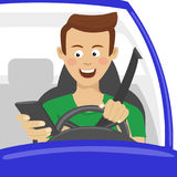 Young man using his smartphone behind the wheel. Problem addiction danger concept. Dangerous situation Royalty Free Stock Photo