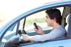 Young man using his smartphone while driving Stock Photography