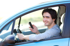 Young man using his smartphone while driving Royalty Free Stock Images