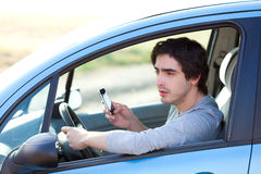 Young man using his smartphone while driving Royalty Free Stock Photography