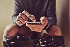 Young man using his smartphone in the toilet. Closeup of a young caucasian man using his smartphone in the toilet while sitting in the bowl Stock Photo