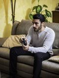 Young man using joystick or joypad for videogames. Attractive young man using joystick or joypad for videogames, sitting on couch at home in his living room Royalty Free Stock Images