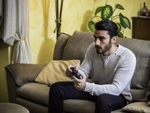 Young man using joystick or joypad for videogames. Attractive young man using joystick or joypad for videogames, sitting on couch at home in his living room Stock Photo