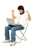 Young man using laptop. Man Sitting in Chair Using Laptop Stock Images