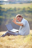 Young man using laptop. Sitting on the grass on the hillside Stock Images