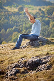 Young man using laptop. Sitting on the grass on the hillside Royalty Free Stock Photo
