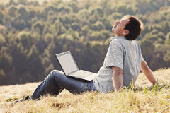 Young man using laptop. Sitting on the grass on the hillside Stock Image